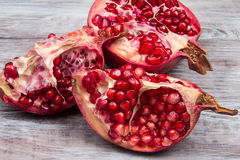 Pomegranate cut into pieces close-up on wooden background Stock Photography