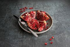 Pomegranate cut into pieces in a plate stock images
