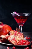 Pomegranate, cut into sections on a metal dish in the background of the shot glasses royalty free stock photo
