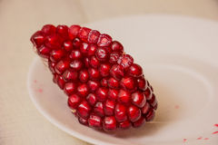 Pomegranate. Cut on a white bowl royalty free stock photos