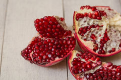 Pomegranate. Cut on wooden background royalty free stock photography