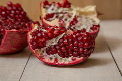 Pomegranate. Cut on wooden background royalty free stock image