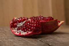 Pomegranate. Cut on wooden background royalty free stock images