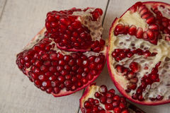 Pomegranate. Cut on wooden background royalty free stock photo