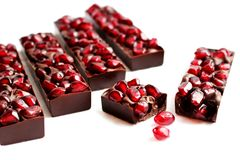 Pomegranate dark chocolate bars on white background stock photography