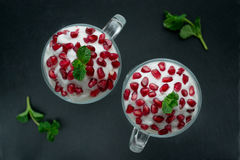 Pomegranate dessert. With cream and mint Stock Photos