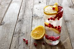 Pomegranate detox water in a glass over rustic wood Stock Photos