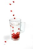Pomegranate fall in water. Pomegranate corns fall to water in glass Royalty Free Stock Image