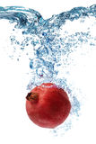 Pomegranate falls deeply under water Royalty Free Stock Photo