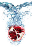 Pomegranate falls deeply under water Royalty Free Stock Photography