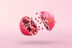 Pomegranate in flight burst. Cut half pomegranate flying in the air. Pomegranate fruit explosion.  stock photos