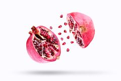 Pomegranate in flight burst on a white background, isolated. Cut half pomegranate flying in the air. Pomegranate fruit. Explosion stock image