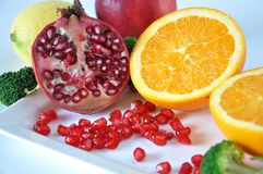Pomegranate and Fresh Orange on White Plate Royalty Free Stock Photos