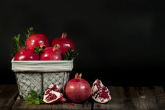 Pomegranate Fruit Basket. Ripe whole pomegranate fruit and green leaves in wire basket. A single whole fruit and  an open pomegranate on wood surface, black Royalty Free Stock Photo