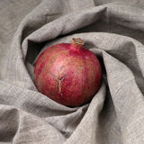 Pomegranate fruit on canvas. Ripe pomegranate fruit on the linen canvas royalty free stock image