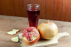 Pomegranate fruit cut dissect and pomegranate juice. On wooden background Stock Image