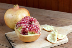 Pomegranate fruit cut dissect. On wooden background Stock Image