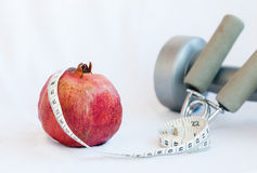 Pomegranate fruit and measuring tape Stock Photography