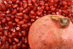 Pomegranate fruit on pomegranate seeds background Royalty Free Stock Image