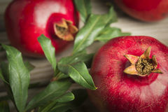 Pomegranate fruits. Close up of some red juicy pomegranate fruits with leaves. Selective focus royalty free stock photos