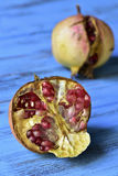 Pomegranate fruits. Some ripe pomegranate fruits on a blue rustic wooden surface royalty free stock photography