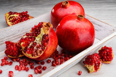 Pomegranate fruits on white wooden background Royalty Free Stock Photos