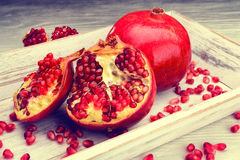 Pomegranate fruits on a white wooden background Stock Image