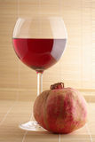 Pomegranate and glass of red wine. Pomegranate and glass of red wine close-up on mat Royalty Free Stock Images