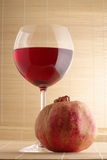 Pomegranate and glass of red wine. Pomegranate and glass of red wine close-up on mat Royalty Free Stock Image