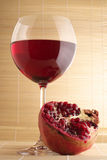 Pomegranate and glass of red wine. Pomegranate and glass of red wine close-up on mat Stock Photo