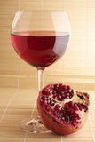 Pomegranate and glass of red wine. Pomegranate and glass of red wine close-up on mat Stock Images