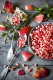 Pomegranate grains on bowl with two silver spoon full of grains on table with pomegranate peel and leaves Royalty Free Stock Image