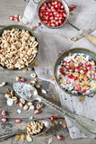 Pomegranate grains on vintage strainer and two bowl of natural yogurt with seed and grains and cereal with spoon Stock Photos