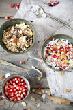 Pomegranate grains on vintage strainer and two bowl of natural yogurt with seed, grains, cereals and muesli with spoon Stock Photography