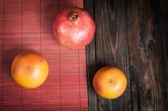 Pomegranate and grapefruit. Fresh fruit. Fruit variety on wood. Food background. Stock Photos