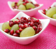 Pomegranate and grapes. Some fresh pomegranate seeds and green grapes royalty free stock photography