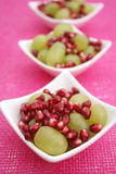 Pomegranate and grapes. Some fresh pomegranate seeds and green grapes stock images
