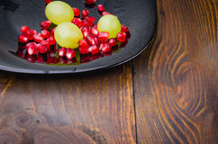 Pomegranate and grapes in a plate. On a wooden background Royalty Free Stock Image