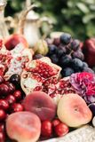 Pomegranate and grapes in a plate on the wooden table stock photos