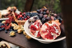 Pomegranate and grapes in a plate on the wooden table royalty free stock photo
