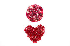 Pomegranate half above seeds in heart shape Royalty Free Stock Images