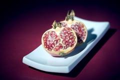 Pomegranate half cut. On white plate on purple background Stock Photo
