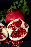 Pomegranate halved. A halved pomegranate exposing ripe red seeds within, and a whole fruit with green leaves behind on black background Royalty Free Stock Photos