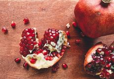 Pomegranate halved and whole. Closeup of ripe pomegranates, one halved and the other whole, on a wooden table background Stock Photography