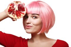 Pomegranate in the hand of a beautiful and cheerful girl in a pink wig and red clothes, on a white background Stock Photos