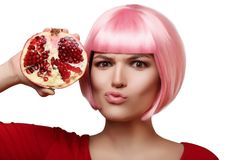 Pomegranate in the hand of a beautiful and cheerful girl in a pink wig and red clothes, on white background, isolated Stock Image