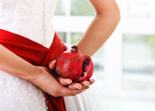 Pomegranate in hands of a bride Stock Image