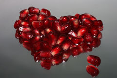Pomegranate heart. A red heart composed from pomegranate seeds on grey background Stock Photography