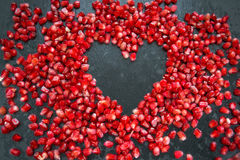 Pomegranate heart on a black background. Scattered ripe pomegranate grains. macro Stock Photo