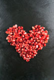 Pomegranate heart. Scattered ripe pomegranate grains. macro. Pomegranate with mint on a black background Stock Image